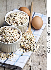 Oat flakes in ceramic bowls and wooden spoon and fresh chicken eggs on rustic wooden table background.