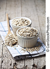 Oat flakes in ceramic bowls and wooden spoon, golden wheat ears on rustic wooden background.