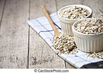 Oat flakes in ceramic bowls and wooden spoon on linen napkin, golden wheat ears on rustic wooden background.