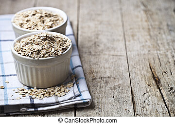 Oat flakes in ceramic bowls on linen napkin, golden wheat ears on rustic wooden background.