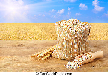 Oat flakes in sack on nature background