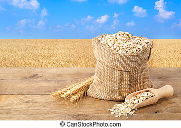 Oat flakes in sack with field on the background