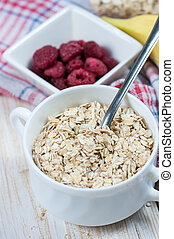 Oat flakes in white bowl on wooden table.