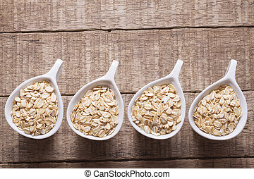 oat flakes in white bowl on wooden table
