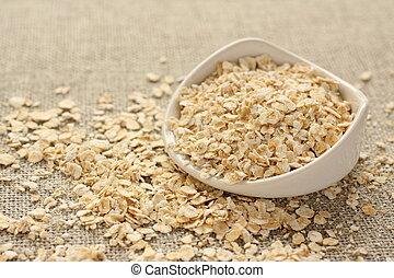 Oat flakes in white ceramic bowl on sackcloth background