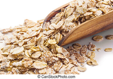 Oat flakes in wooden scoop isolated on white
