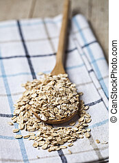 Oat flakes in wooden spoon on linen napkin, golden wheat ears on rustic wooden background.