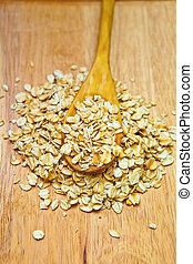 Oat flakes on a wooden spoon