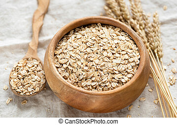 Oat flakes, rolled oats in wooden bowl