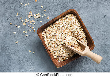 Oat flakes, rolled oats in wooden bowl with scoop