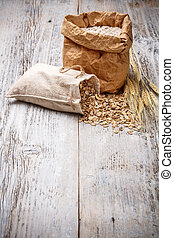 Oat flakes spilling from the burlap bag on old wooden table