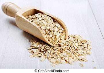 Oat flakes in wooden scoop on white wooden background