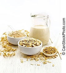 Oat flakes with flour and milk on white board
