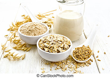 Oat flakes with flour and milk on white wooden board