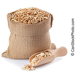 oat grains in bag and oat flakes in wooden scoop