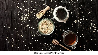Oat in glass jar with honey - From above view of oat and...