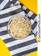 Oat meal in bowl on kitchen towel and bright yellow background with copy space