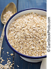 oat on white bowl on blue wooden background