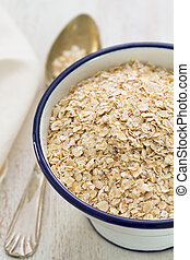 oat on white bowl on white wooden background