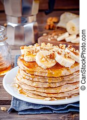 Oat pancakes with banana, walnuts and maple syrup