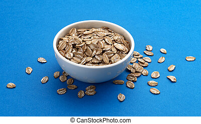 Oat rye flakes in bowl isolated on blue color background