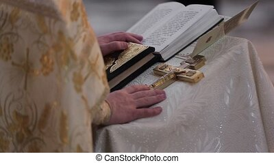 Oath at the newlyweds on luxuriously decorated bible. Hands of men  in the church near the altar, the priest cross.