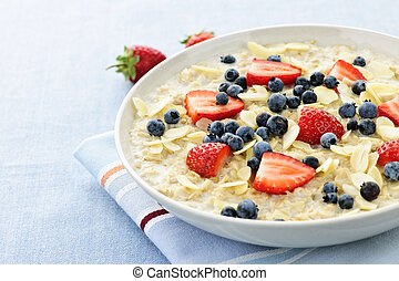 Oatmeal breakfast cereal with berries - Bowl of hot oatmeal ...