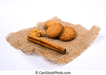 oatmeal cookies, cinnamon and walnuts on burlap and white background