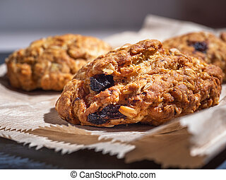 Oatmeal cookies with cereals and raisins on a paper bag, close-up.