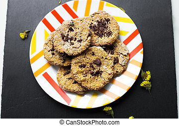 Oatmeal cookies with chocolate on a colorful plate