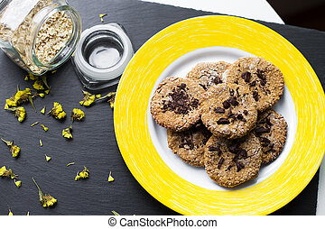Oatmeal cookies with chocolate on a yellow plate