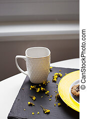 Oatmeal cookies with chocolate on bright yellow plate and cup of coffee.