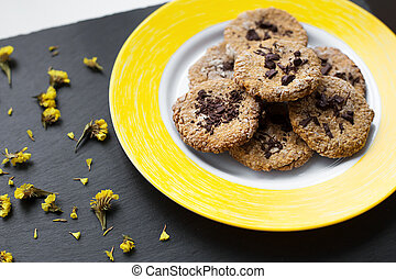 Oatmeal cookies with chocolate on bright yellow plate.