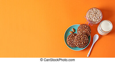 Oatmeal cookies with nuts on a plate, cup of milk
