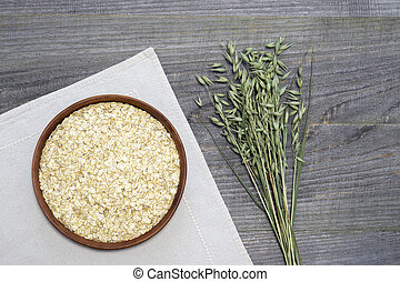 Oatmeal flakes in a ceramic bowl on a white linen napkin and green ears of oats on a rustic wooden table background.