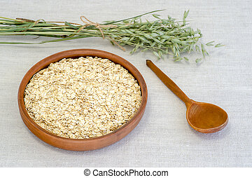 Oatmeal flakes in a ceramic bowl with a wooden spoon and ears of oats on a light linen tablecloth.