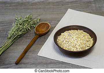 Oatmeal flakes in a ceramic bowl with a wooden spoon and ears of oats on a linen napkin on a wooden table background.