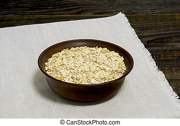 Oatmeal flakes in a ceramic brown bowl on a light linen napkin on a dark wooden table background.
