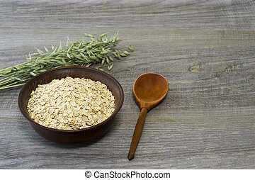 Oatmeal flakes in a ceramic brown bowl with a wooden spoon and ears of oats on a rustic wooden table background.