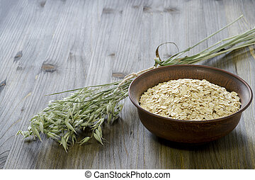 Oatmeal flakes in a ceramic brown bowl with green ears of oats on an old faded gray wooden table background.