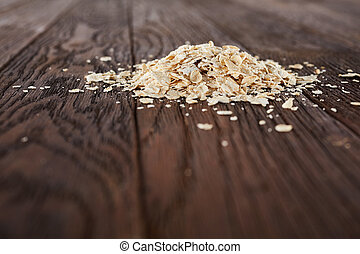 Oatmeal flakes on a wooden background. Top view.