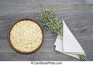 Oatmeal flakesl in a ceramic bowl on a rustic wooden table background and green ears of oats in a white linen napkin.