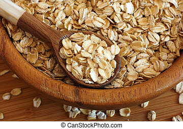 Oatmeal in a bowl with a wooden spoon.