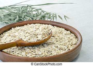 Oatmeal in a brown ceramic bowl with a wooden spoon on a background of green ripe ears of oats on a linen tablecloth.