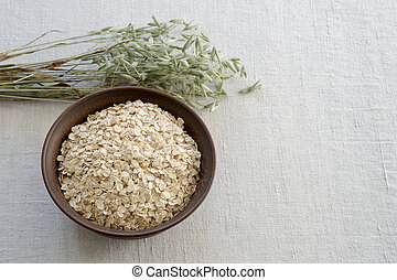 Oatmeal in a brown ceramic bowl with on a background of green ripe ears of oats on a linen tablecloth.
