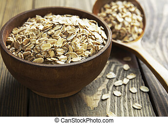 Oatmeal in a brown wooden bowl on the table