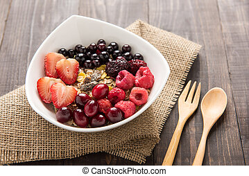 Oatmeal in bowl topped with fresh blueberries, cranberries, strawberries, raspberries, blackberries for healthy breakfast.