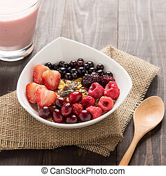 Oatmeal in bowl topped with fresh blueberries, cranberries, strawberries, raspberries, blackberries and berry smoothie.