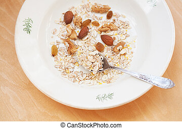 oatmeal in white bowl with nuts on orange napkin