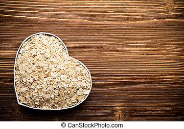 Oatmeal, heart-shaped box. Wooden surface.